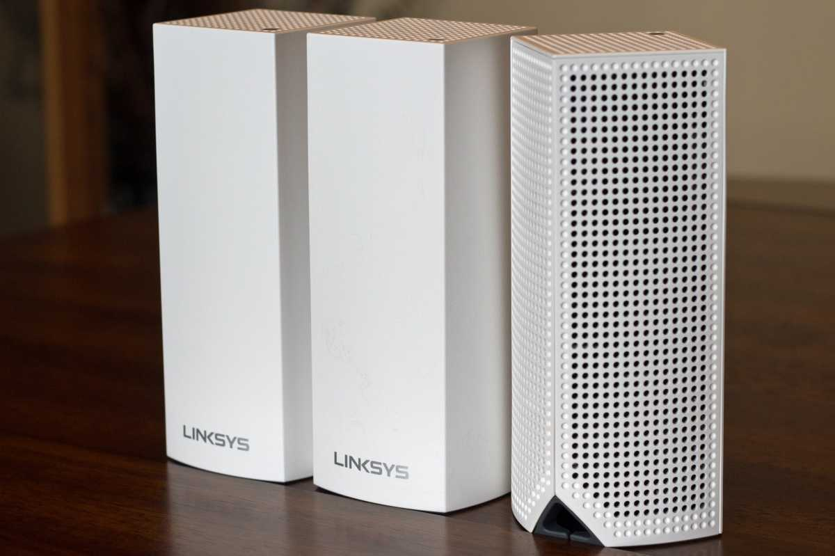 Three Linksys Velop mesh nodes next to each other, with one turned to show the back view
